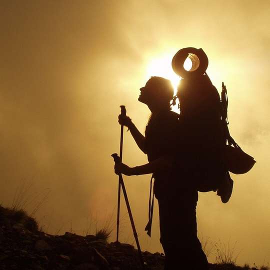 Hiker with trekking poles standing in a halo of sun