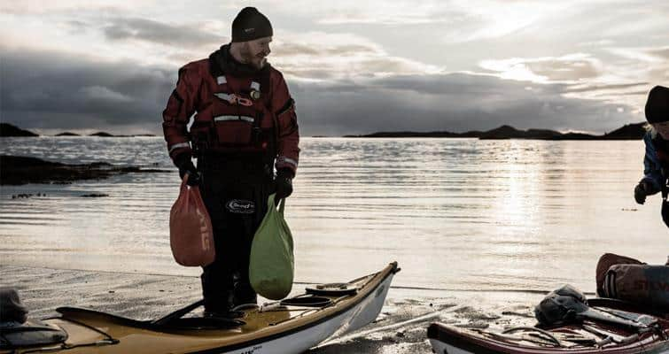 mAN LOADING KAYAKS WITH DRY BAGS